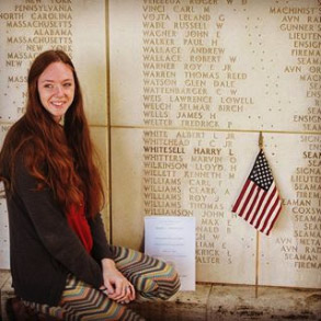 A woman kneels next to memorial wall