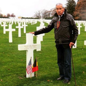Elderly man wearing a medal standing by gravestone marker