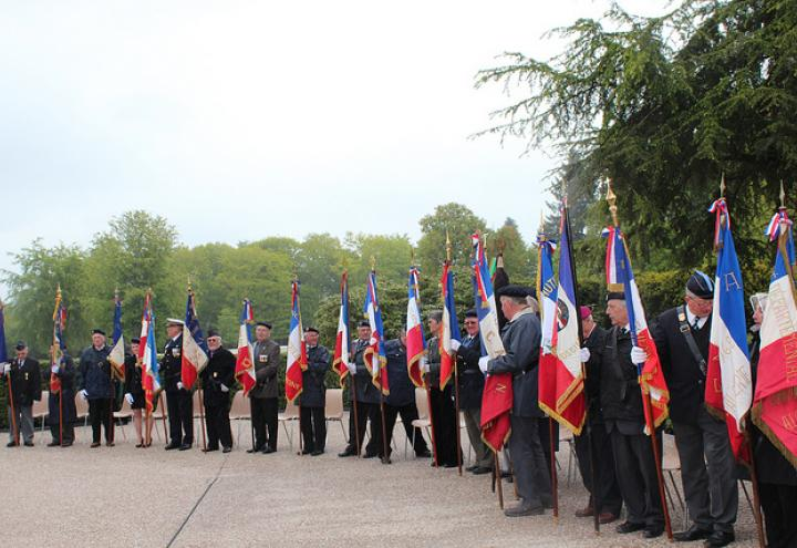 Participants stand with flags during ceremony.