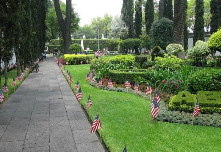 American flags line the pathway and floral beds at the cemetery.