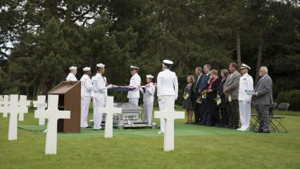 Sailors and family members stand during this solemn ceremony.