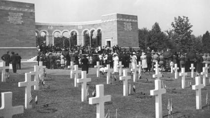 Historic photo shows headstones with flags and a crowd gathered in the memorial area.
