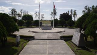 A distant view of the Cabanatuan American Memorial shows the entire plaza including a concrete pathway and two flags poles.