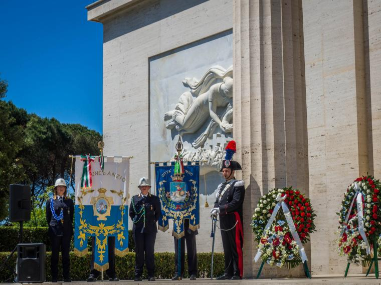 Men and women in uniform stand next to the city banners for Anzio and Nettuno.