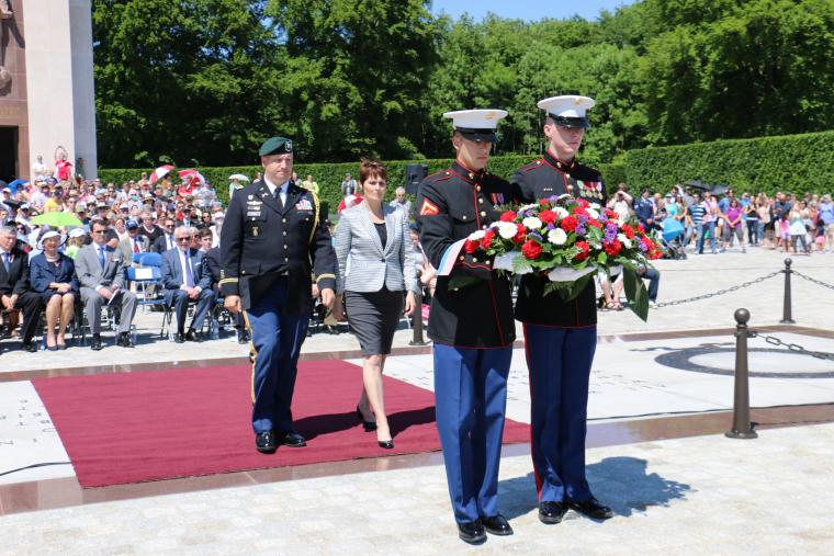 Two Marnes carry a floral wreath, followed by Evans and Shorter-Lawrence, who will lay the wreath.
