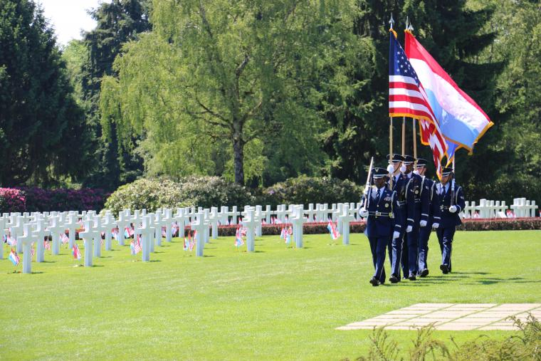 Men and women in uniform march through the cemetery.