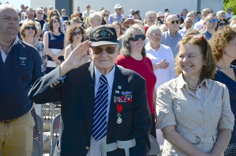 A man in a suit stands and salutes.