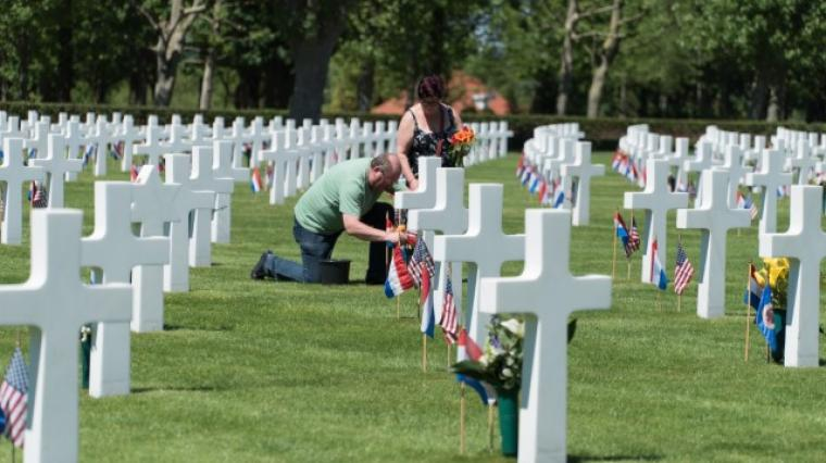 A man and woman place flowers at a headstone.