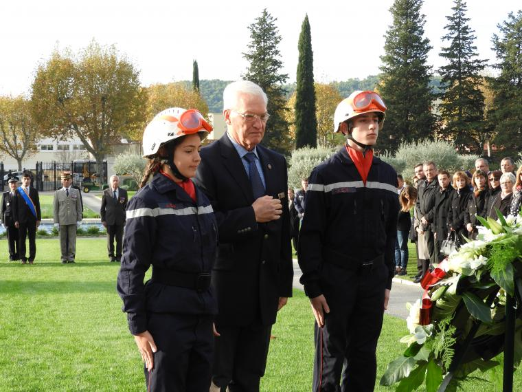 A woman and two men pause after the wreath laying.