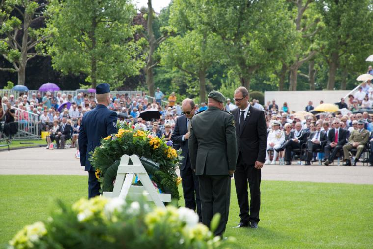 Men in suits pause after laying a floral wreath.