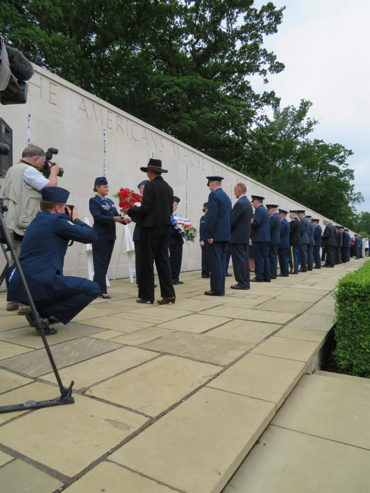A long line of people prepare to lay wreaths at the Wall of the Missing.