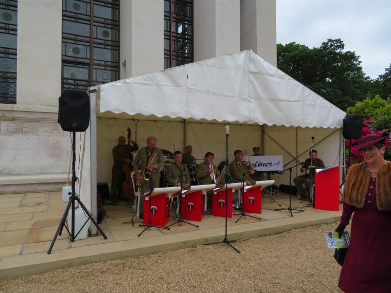 Members of a band sit under a tent, and play.