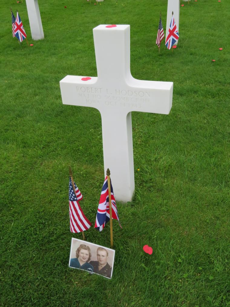 A photo, along with an American and British flag, are in front of a headstone.