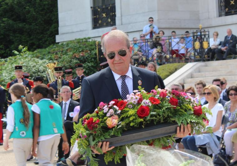 Man in a suit prepares to lay a wreath.