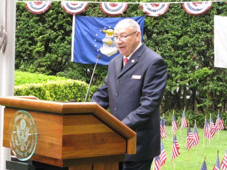 De Jesus stands at a podium to deliver remarks.