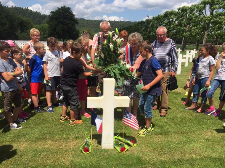 Students and adults place a larger flower arrangement at the headstone.
