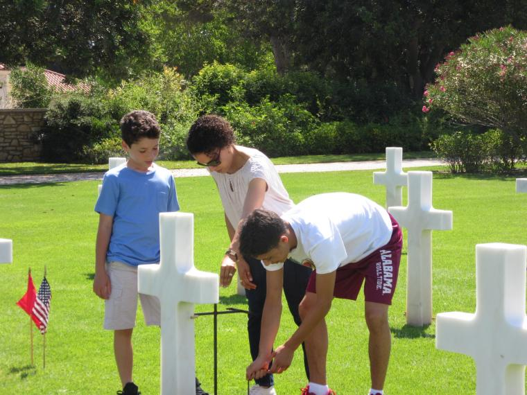 A woman and two boys help place the flags.