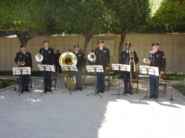 Soldiers in uniform stand with their instruments.