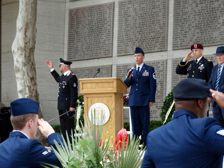 An airman sings the national anthem from the podium area.