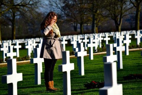 A woman salutes a headstone with a wreath.