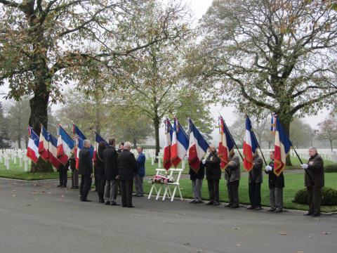 Flag bearers flank the wreath as town officials present it during the ceremony.