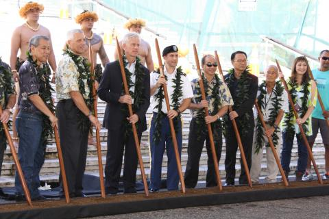 Men and women stand with wooden sticks for the ceremony.