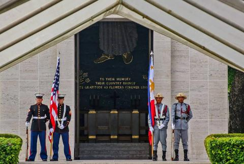 Members of the American and Philippine military stand with flags and weapons outside the chapel building.