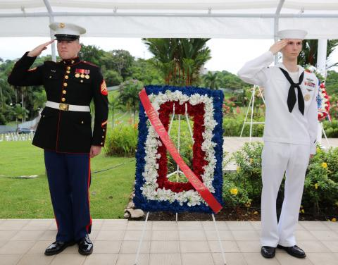 A marine and a sailor salute next to a floral wreath.