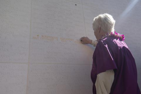 Alexandra Bonnyman places a bronze rosette next to her father's name.