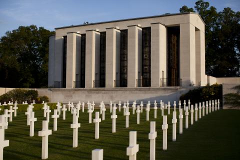 Lines of headstones fill the foreground in front of the memorial building.