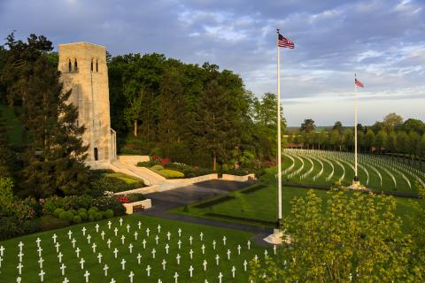 Headstones and two flag poles dot the landscape in front of the chapel.