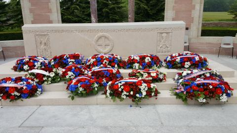 Floral wreaths lay on the steps of the memorial.