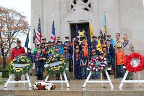 Boy Scouts stand in front of the chapel and behind the floral wreaths.