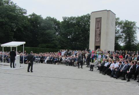 Most crowd members sit during the Memorial Day ceremony.