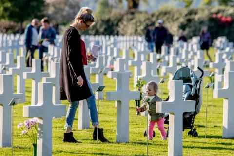 A toddler carries a white rose, amidst the headstones.