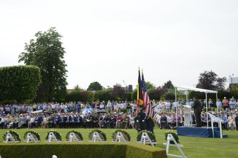 Attendees stand and sit while a man speaks from the podium.