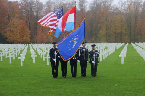Honor Guard participants stand with firearms or flags in the plot area.