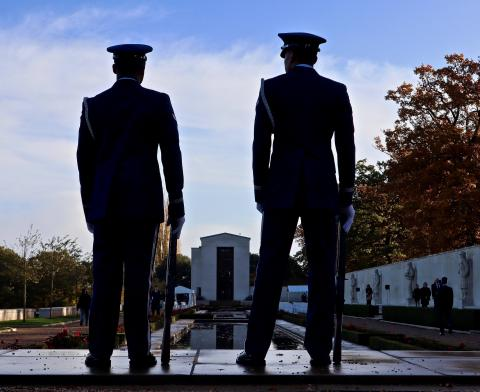 Two airmen stand and face the chapel building.