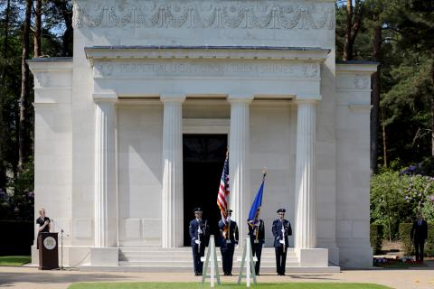 A U.S. Color Guard stands with flags and rifles outside the chapel.