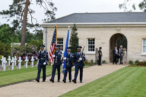 Men in uniform carry a flag or a rifle as part of the Honor Guard.