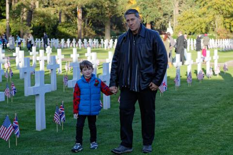 A father holds his son's hand in the plot area.
