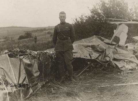 Historic photo showing man in uniform in front of destroyed plane.