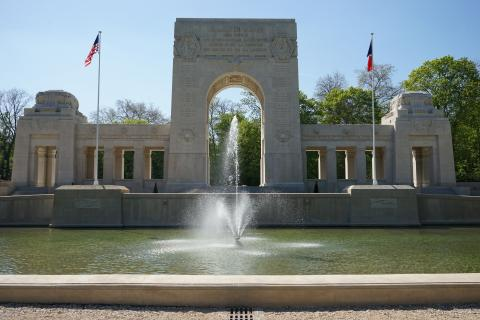 A large fountain is in front of the memorial cemetery building.