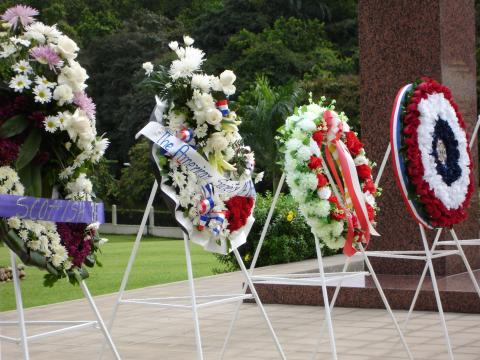 Four large floral wreaths rest on stands after the ceremony.