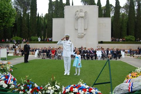 Man in uniform and little girl salute.