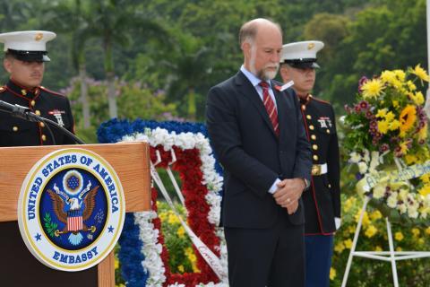 Ambassador Farrar stands next to the podium.