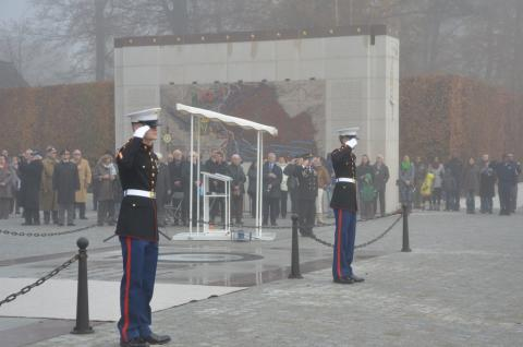 Marines salute as ceremony attendees look on.