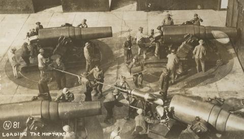 Historic photos shows men loading large mortars.