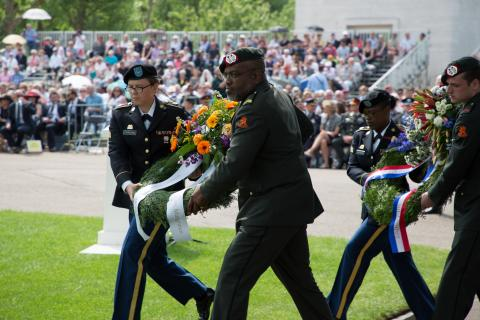 Men and women in uniform carry floral wreaths.