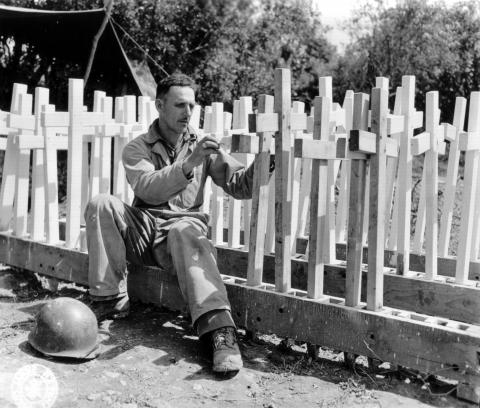 Historic photo shows soldier preparing wooden crosses.